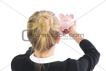 Blonde young cute businesswoman holding a piggy bank