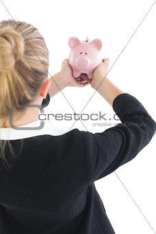 Blonde businesswoman showing a piggy bank