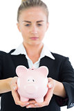 Serious young businesswoman holding pink piggy bank