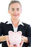 Pretty businesswoman holding pink piggy bank