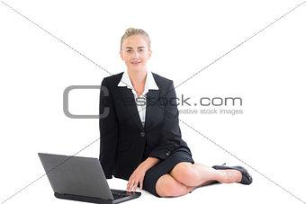 Attractive blonde businesswoman sitting on floor using her notebook