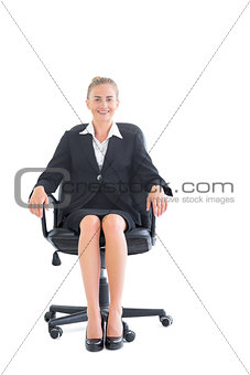 Content young businesswoman sitting on an office chair