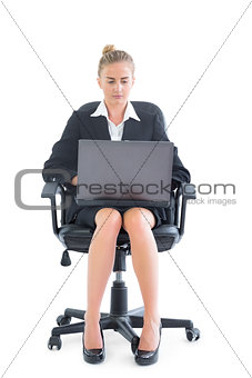 Beautiful businesswoman sitting on an office chair using her notebook
