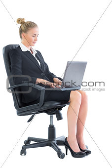 Focused chic businesswoman sitting on an office chair using her laptop