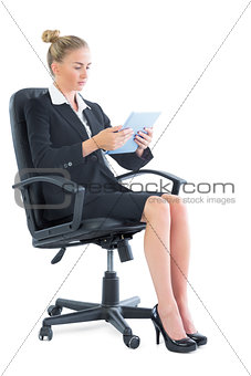 Focused young businesswoman sitting on her office chair