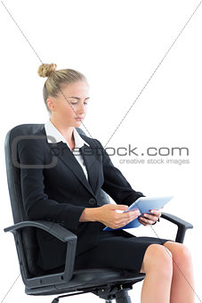 Focused young businesswoman making use of her tablet