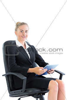 Attractive well dressed businesswoman sitting on an office chair holding a tablet