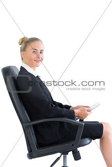 Gorgeous young businesswoman sitting on an office chair holding her tablet