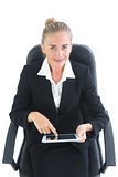 Smiling blonde businesswoman sitting on her office chair