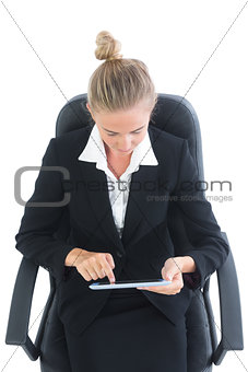 Concentrated young businesswoman using her tablet