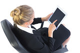 Busy businesswoman sitting on an office chair using her tablet
