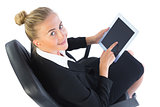 Cheerful young businesswoman using her tablet sitting on an office chair