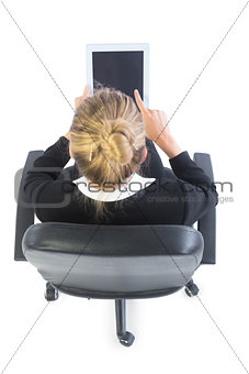 Blonde young businesswoman sitting on an office chair