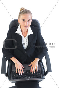 Cute young businesswoman sitting on an office chair using her notebook