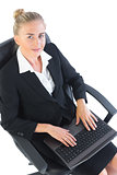 Young businesswoman sitting on her office chair using her notebook