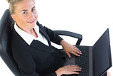 Happy young businesswoman sitting on an office chair using her notebook