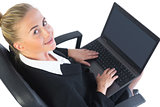 Cute businesswoman using her notebook sitting on an office chair