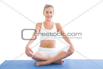 Toned smiling blonde sitting in lotus pose