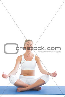 Toned meditating blonde sitting in lotus pose