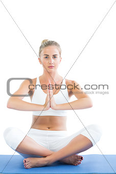 Toned focused blonde sitting in lotus pose meditating