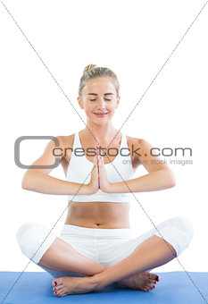 Toned smiling blonde sitting in lotus pose meditating