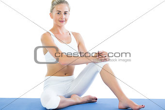 Toned smiling blonde sitting on exercise mat