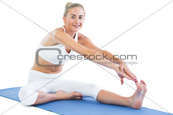 Toned smiling blonde sitting on exercise mat stretching right leg