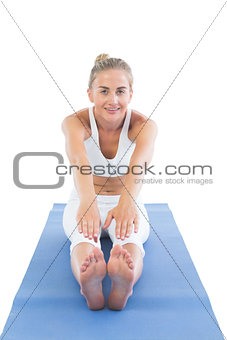 Toned smiling blonde sitting on exercise mat stretching legs