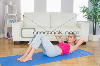 Sporty happy blonde doing sit ups