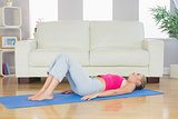 Sporty tired blonde lying on exercise mat
