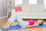 Sporty exhausted blonde lying on exercise mat