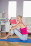 Smiling sporty blonde model sitting on blue exercise mat