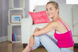 Sporty smiling blonde model sitting on blue exercise mat
