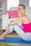 Sporty cheerful blonde model sitting on blue exercise mat