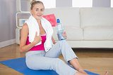 Happy sporty blonde sitting on exercise mat holding water bottle