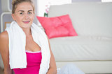 Happy blonde sitting on floor with towel around neck