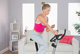 Sporty focused blonde training on exercise bike listening to music