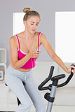Sporty blonde training on exercise bike listening to music