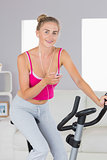 Sporty smiling blonde training on exercise bike listening to music