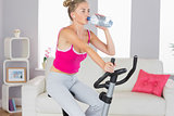 Sporty determined blonde training on exercise bike drinking water