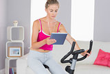 Sporty focused blonde training on exercise bike using tablet