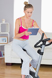 Sporty serious blonde training on exercise bike using tablet