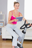 Sporty smiling blonde training on exercise bike using tablet