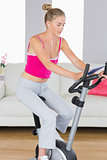Sporty unsmiling blonde training on exercise bike using tablet