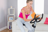 Sporty unsmiling blonde training on exercise bike reading a book