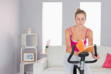 Sporty focused blonde training on exercise bike reading a book