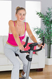 Sporty cheerful blonde training on exercise bike