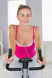 Portrait of sporty cheerful blonde training on exercise bike