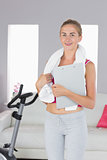 Sporty smiling blonde holding clipboard and towel