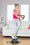Sporty determined blonde training on step machine